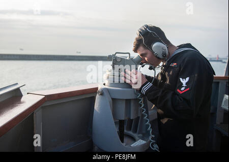 151030-N-XM324-006BUSAN, Republic of Korea (Oct. 30, 2015) Quartermaster 3rd Class Christian Bobbish, from New Baltimore, Mich., takes a navigational bearing as the Arleigh Burke-class guided-missile destroyer USS Fitzgerald (DDG 62) arrives in Busan. Fitzgerald is participating in bilateral training with the Republic of Korea Navy to strengthen the U.S.-ROK alliance and improve regional security. (U.S. Navy photo by Mass Communication Specialist 3rd Class Patrick Dionne/Released) - Stock Photo