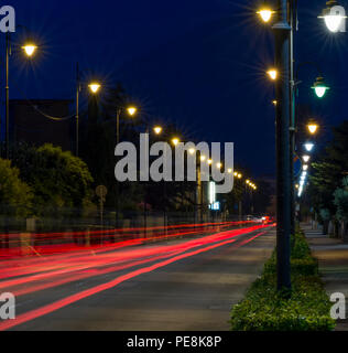 Busy avenue with light trails of cars in the blue hour - Stock Photo