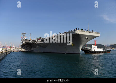 151030-N-AD372-102 BUSAN, Republic of Korea (Oct. 30, 2015) Sailors assigned to the Nimitz class aircraft carrier USS Ronald Reagan (CVN 76), man the rails as the ship pulls into Busan. Reagan is the Navy's only forward deployed aircraft carrier and is conducting a scheduled port visit while participating in bilateral training with the ROK Navy to strengthen the U.S.-ROK alliance and improve regional stability. Ronald Reagan and its embarked air wing, Carrier Air Wing (CVW) 5, provide a combat ready force that protects and defends the collective maritime interests of the U.S. and its allies an - Stock Photo