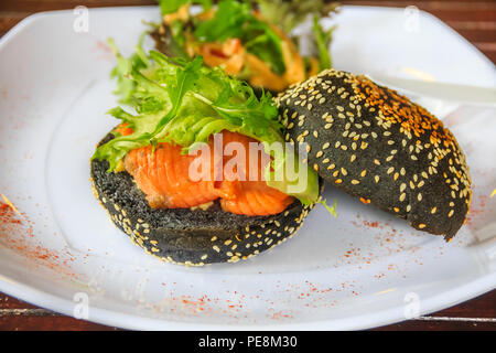 Salmon and egg sandwich on a toasted charcoal bun with sesame seed in Singapore on a plate decorated with paprika - Stock Photo