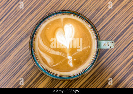 Close-up of coffee latte and cappuccino with heart shape in milk froth in cup as flat lay from above - Stock Photo