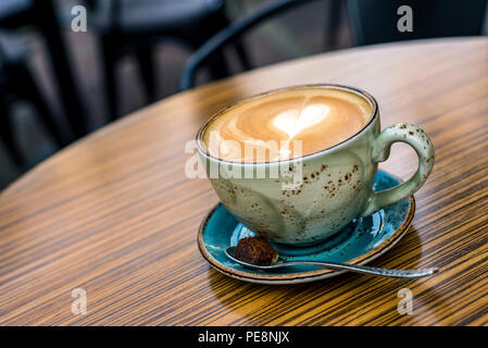 Close-up of cup with coffee latte and cappuccino with heart shape in milk froth from above as background - Stock Photo