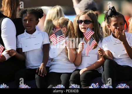 Children wave American flags from a float during the 20th Annual Veterans Day Parade in Jacksonville, NC, Nov. 7, 2015. The Veterans Day Parade, hosted by Rolling Thunder Inc. Chapter NC-5, was observed by veterans, Service members and residents of Jacksonville and showed support for members of the armed forces. (U.S. Marine Corps photo by Staff Sgt. Neill A. Sevelius) MCIEAST-MCB CAMLEJ Combat Camera/Released) - Stock Photo