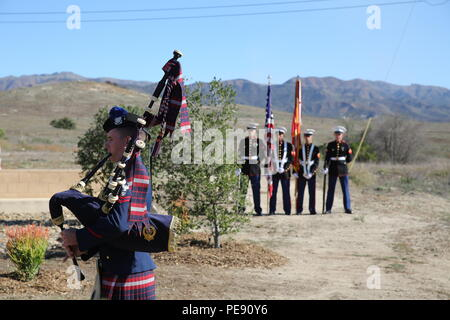 U.S. Coast Guard Petty Officer 2nd Class Jeremy Cook, left, plays 'Amazing Grace' on a set of bagpipes during a ceremony honoring members of 2nd Battalion, 1st Marine Regiment who gave their lives during the Vietnam War. During the ceremony, plaques bearing the names of the fallen were dedicated in their honor at the Camp Horno Memorial Garden aboard Camp Pendleton. (U.S. Marine Corps photo by Sgt. Paris Capers/ Released) - Stock Photo