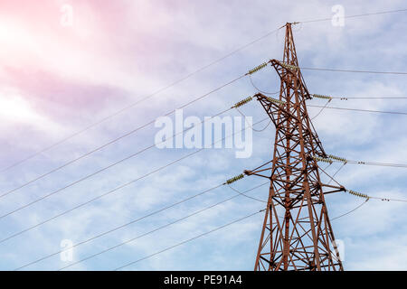 Old aged rusty triangle metal plate with High voltage warning sign. Power station with transformers and electricity distribution lines. Keep out. - Stock Photo