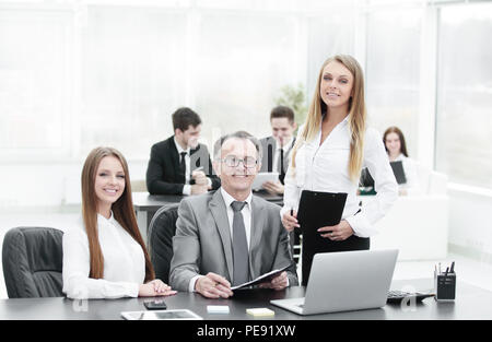 Director and assistants near the desktop in the office - Stock Photo