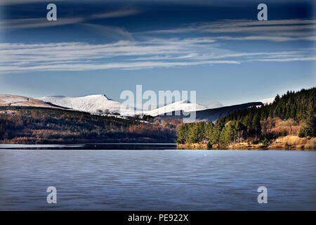 Brecon Beacons mountains in snow rising above Pontsticill Reservoir, Brecon Beacons National Park, Wales, UK Stock Photo
