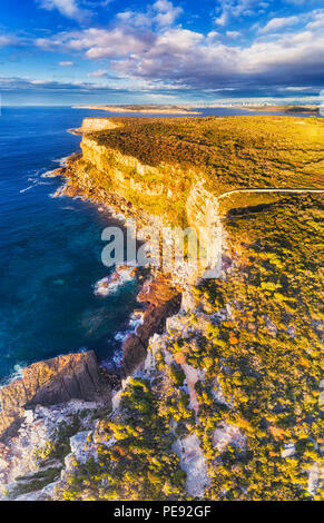 Rugged steep cliffs on pacific facing coast of North Head in Sydney - aerial elevated view from edge cliff up to horizon, sky and city CBD.