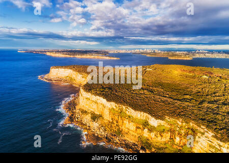 Steep endges of North Head sandstone plateau guarding SYdney harbour from open pacific ocean on a sunny morning with view of distant city CBD.