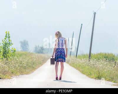 Young woman runaway with suitcase - Stock Photo
