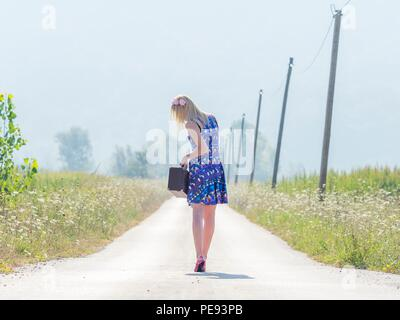Young woman runaway with suitcase country-side countryside in on at near - Stock Photo