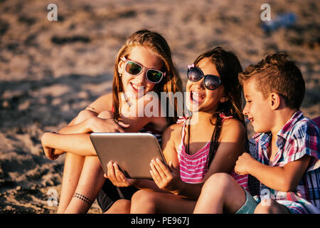 Portrait of positive children playing with digital tablet on sandy beach together - Stock Photo