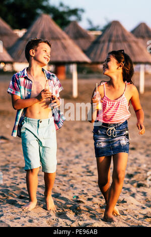 Portrait of happy children while having fun walking on the shore. Summer vacation and healthy lifestyle concept - Stock Photo