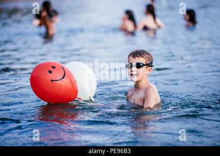 Happy child playing and swimming in the sea with balloons. Summer vacation concept - Stock Photo
