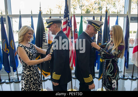 151113-N-HD670-349 PORT HUENEME, Calif. (Nov. 13, 2015) – Capt. Steven Kelley and Capt. Ronald Gruzesky watch as their wives transfer their command ashore pins during 1st Naval Construction Regiment's (1 NCR)  change of command ceremony. During the ceremony, Kelly relieved Gruzesky as commodore of 1 NCR. The 1 NCR exercises peacetime command and control over Naval Mobile Construction Battalions (NMCB) 18, based at Fort Lewis, Wash., NMCB 22, in Fort Worth, Texas, and NMCB 25 in Port Hueneme. (U.S. Navy photo by Utilitiesman 3rd Class Stephen Sisler/Released) - Stock Photo