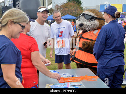 Rear Adm. Steven P. Metruck (left) and Master Chief Petty Officer Mark Pearson (right) talk with shipmates and Sammy the Sea Otter, Saturday, Nov. 7, 2015, during Coast Guard Day festivities in Portsmouth, Va. The city of Portsmouth is a designated Coast Guard City and held a festival to honor the men and women of the service and their families. (Coast Guard photograph by Petty Officer 3rd Class Joshua Canup)
