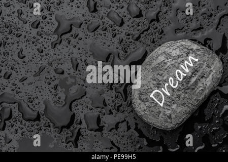 Conceptual image with the word dream written on a stone, on a black background sprinkled with rain droplets. - Stock Photo