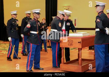 Staff Sgt. Paul J. Miller holds a plate while Col. Peter D. Buck cuts a traditional birthday cake at the Headquarters and Headquarters Squadron 240th Marine Corps Birthday Ball held at the Marriot Resort and Spa in Hilton Head, S.C., Nov. 6, 2015. Cutting the cake is a Marine Corps tradition, celebrating the birth of the Corps. (U.S. Marine Corps photo by Lance Cpl. Kayla L. Douglass/Released) - Stock Photo