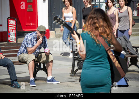 man eating ice cream sitting on bench listening to female busker in abbey churchyard Bath England UK - Stock Photo