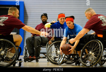 Members of the American Red Cross and Headquarters Wounded Transition Unit teams go for a ball during a tournament Nov. 13, 2015, at Ramstein Air Base, Germany. Airmen and Soldiers learned how wheelchair basketball levels the playing field and encourages competition and camaraderie. (U.S. Air Force photo/Staff Sgt. Armando A. Schwier-Morales) - Stock Photo