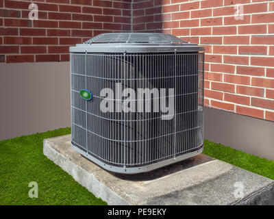 Air conditioning and heating unit outside of a home - Stock Photo