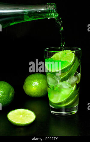Glass of cold green lemonade with ice and fresh ripe green limes on black background. Homemade lemonade. Mojito or tarragon cocktail. Spring and summe - Stock Photo