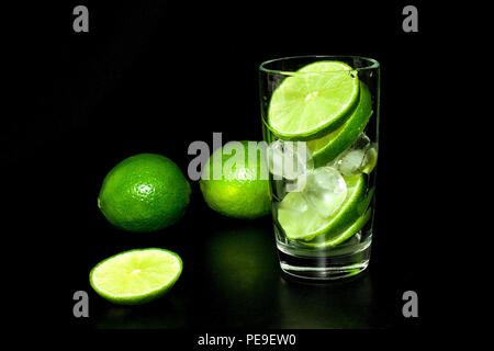 Glass with ice and fresh ripe green limes on black background. Preparation of lemonade. Mojito cocktail. Spring and summer refreshing and beverages co - Stock Photo