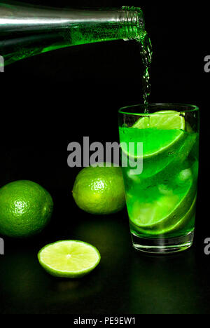 Summer refreshing and beverages concept. Stream of cold lemonade water from a bottle is poured into a glass cold drink with ice and fresh ripe slice g - Stock Photo