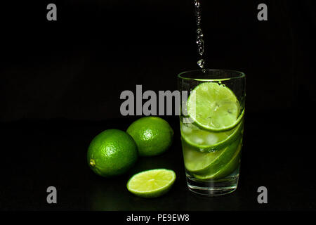 Summer refreshing and beverages concept. Stream pours into a glass of cold drink with ice and fresh ripe slice green limes on black background. Homema - Stock Photo