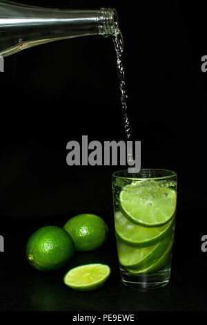Summer refreshing and beverages concept. Stream of cold water from a bottle is poured into a glass with ice and fresh ripe slice green limes on black  - Stock Photo
