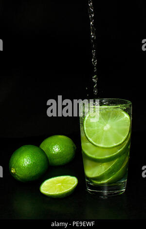 Summer refreshing and beverages concept. Stream of water is poured into Glass of cold drink with ice and fresh ripe slice green limes on black backgro - Stock Photo