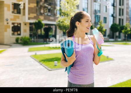 Joyful happy woman holding a bottle of water - Stock Photo