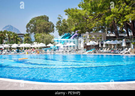 Large pool with waterslides under blue summer sky. Mountains and pines in background - Stock Photo