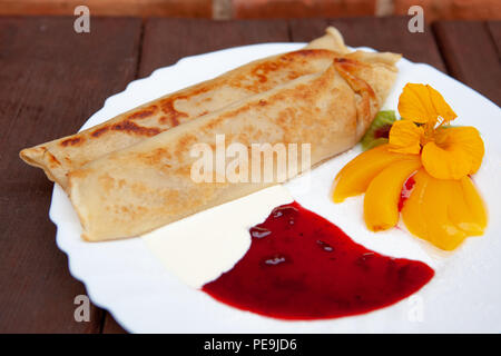 White plate with pancakes pancakes, with jam, cream, fruit and flower on a wooden table - Stock Photo