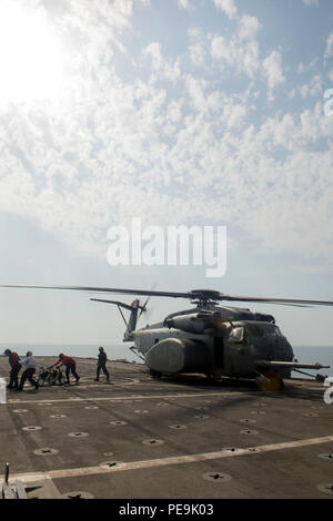 151119-N-BJ294-048 ARABIAN GULF (Nov. 19, 2015) Crewmembers, assigned to Helicopter Mine Countermeasures Squadron (HM-15), clear the flight deck after loading a set of unmanned underwater vehicles onto an MH-53E Seadragon during U.S.-UK Mine Countermeasures Exercise (MCMEX). U.S.-U.K. MCMEX is designed to improve interoperability, and evolve the expeditionary mine countermeasures company concept of employment from an Afloat Forward Staging Base and afloat platforms of opportunity. (U.S. Navy photo by Mass Communication Specialist Wyatt Huggett/Released) - Stock Photo
