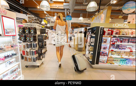Woman air traveller shopping in the duty free shop, duty free shop, Bordeaux-Merignac airport, Bordeaux, France Europe - Stock Photo