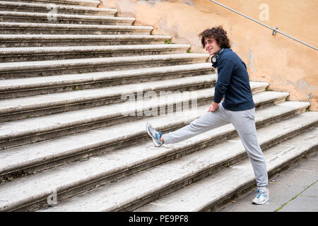 Handsome young sportsman stretching and warming-up for training on staircase - Stock Photo