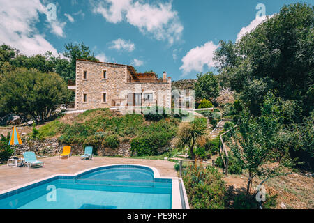 Mesonisia, Rethymno, Crete - August 2018: View towards villa Krios with swimming pool on a sunny day with blur sky. Krios Villa is a resort located in - Stock Photo