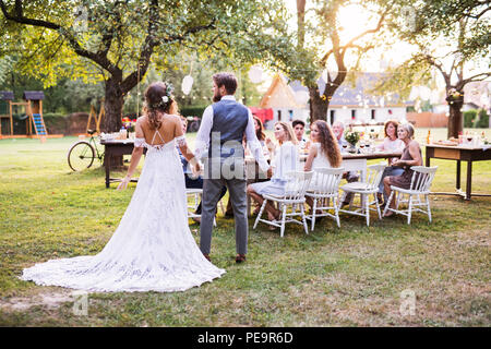 Bride and groom holding hands at wedding reception outside in the backyard. - Stock Photo