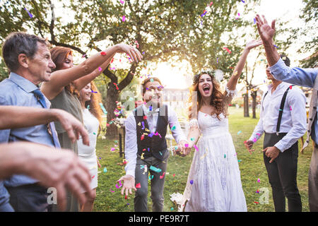 Bride, groom and guests throwing confetti at wedding reception outside. - Stock Photo