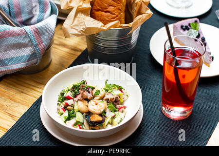 Lunch with seafood salad, drink, bread on the table in the cafe - Stock Photo