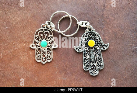 Two key rings in the form of Fatima Hand on a brown leather background. Ancient symbol and traditional modern tourist souvenir of Tunisia. - Stock Photo