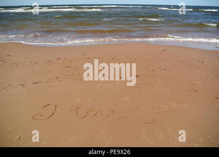 Words 'I love you' beautifully handwritten on red sand on a beach with the sea, sky and waves in the upper part, Prince Edward Island - Stock Photo