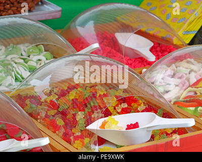 Close up of colorful gummy sweets bears in market with white plastic scoops