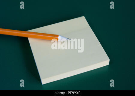 stick note with pencil on green blackboard background. Copyspace. - Stock Photo