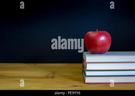 Back to school background with books and red apple over desk front ochalkboard background. - Stock Photo