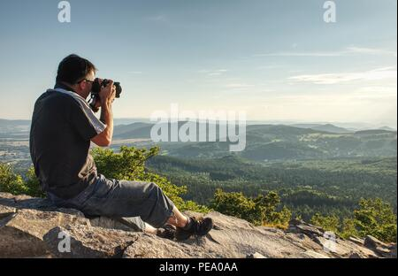 Nature photographer create art on view point in mountains. Man looking into viewfinder of his big camera, taking photo of borning amazing day. - Stock Photo