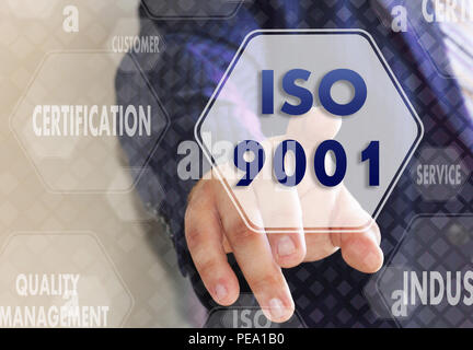 The businessman chooses ISO 9001,  presses a button on the touch screen - Stock Photo