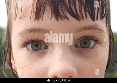 Closeup of a child with big green eyes and an intense scared gaze - Stock Photo