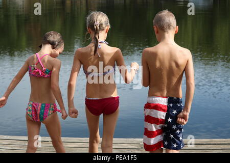 Three wet children in their swimsuit seen from behind on a dock by the water - Stock Photo